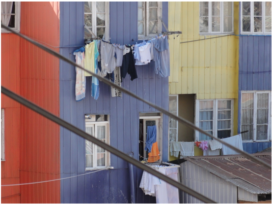 Laundry hanging outside colorful house.