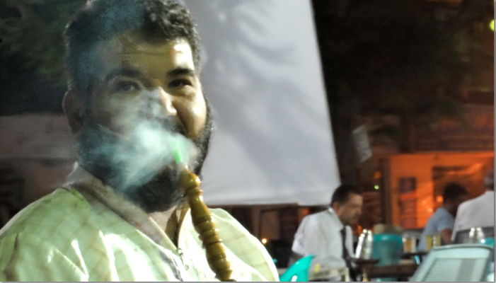 man smoking sheesha in coffee shop