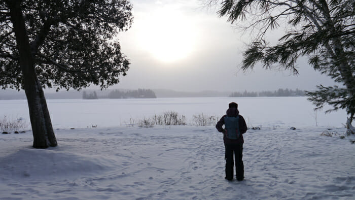 woman standing in snow at dusk, winter retreat