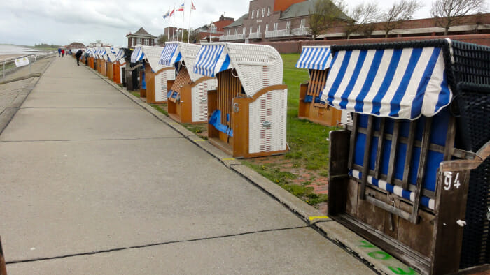 A line of German beach chairs from which to enjoy the beach but be protected from the wind.