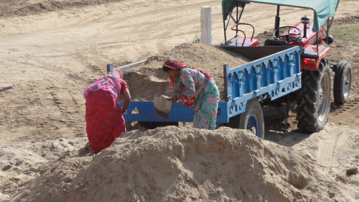Women loading a dump truck with sand using buckets.