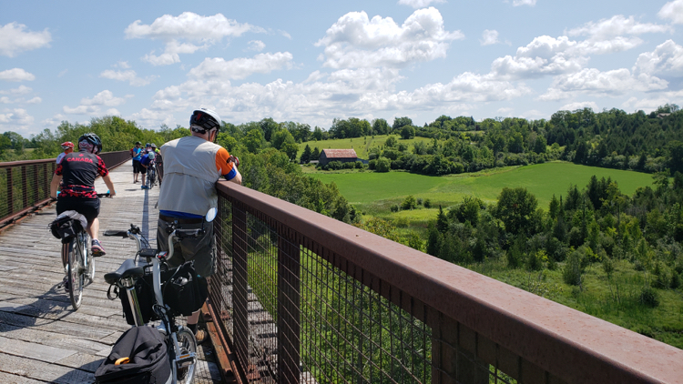Man looking out over countryside from a rail trail bridge.